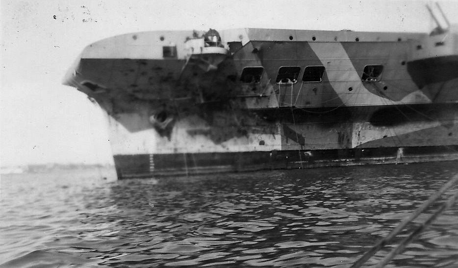 The scarred port bow of HMS ILLUSTRIOUS is seen in this picture believed to have been taken shortly after arriving in Alexandria.