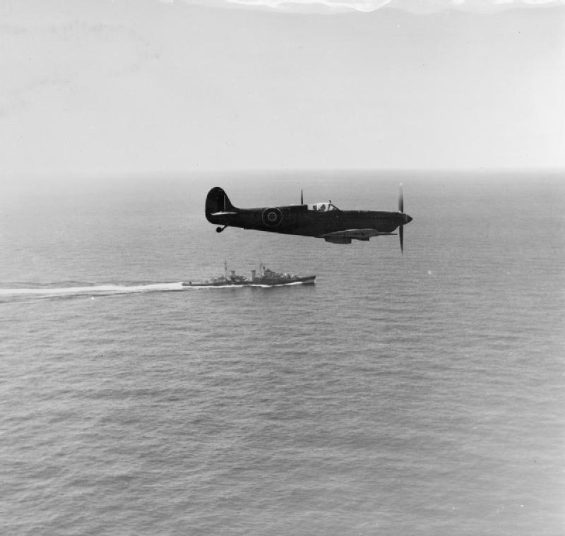 A Supermarine Seafire of No 807 Squadron Fleet Air Arm flying above the British cruiser HMS ROYALIST during a training flight from the Royal Naval Air Station at Dekhelia, Egypt.
