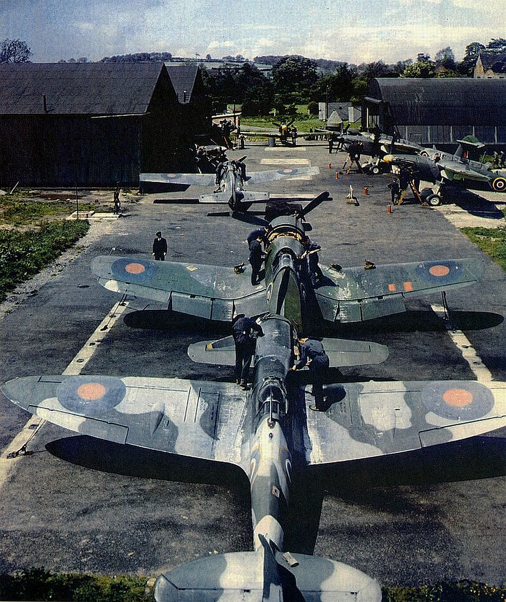 A line-up of Fleet Air Arm aircraft at RNAS Mill Meece / HMS Fledgling  in 1943/44. The facility was used to train WRNS Air Mechanics (Ordnance) on FAA types: Shown here is a Seafire MkI, front, and a Corsair with a Martlet in the middle ground. Off the track to the right are two Fairy Barracudas. Facing the camera at the top of the image is probably a Sea Hurricane though it may be a Fulmar.