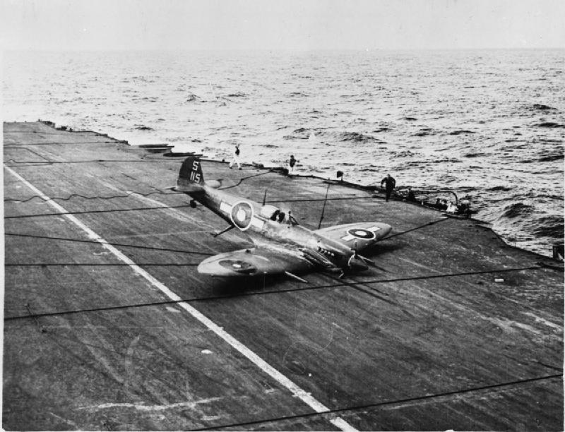 "A successful ""belly landing"" by a British Pacific Fleet Supermarine Seafire, whose undercarriage was damaged during on operation against the Japanese. Photograph possibly taken on board HMS INDEFATIGABLE. Note the arrester wires lying across the deck."