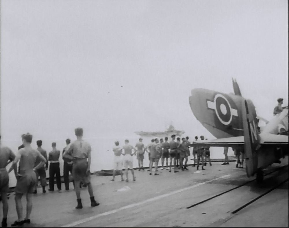 Deck handling crew mill about aboard HMS IMPLACABLE, with a folded FireFly sitting on the dual-track catapult.