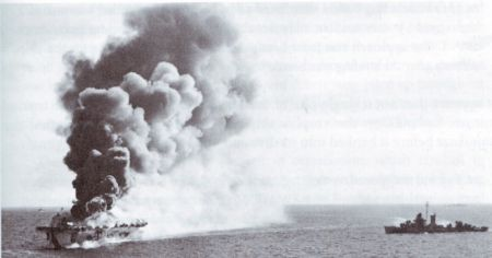 The escort carrier  Ommaney Bay burns after being hit by a kamikaze.