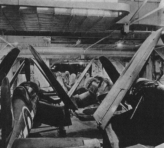 Corsairs in British Pacific Fleet markings sit inside HMS FORMIDABLE'S hangar.