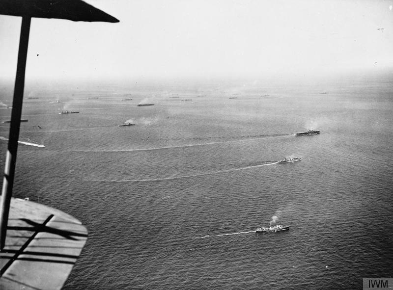 A view of the Pedestal convoy from the air, showing HMS EAGLE hauling out of the formation with cruiser and destroyer support for flying operations, with the merchant ships with either NELSON or RODNEY in the background.