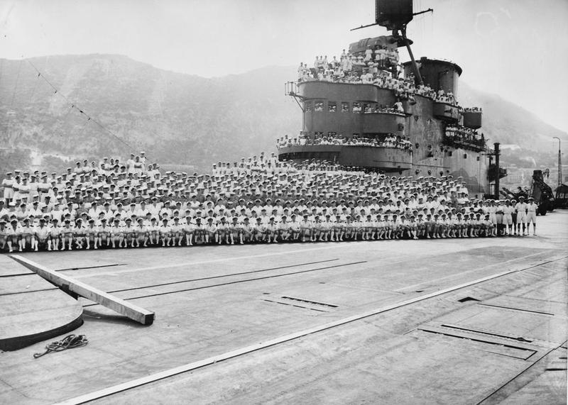 The ship's company of HMS INDOMITABLE pose for a photograph after escorting the Malta Pedestal convoy. The buckled forward lift can be seen in the left foreground.