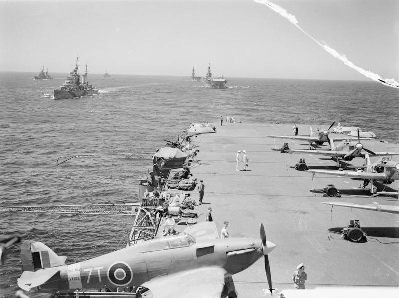 A Sea Hurricane on an outrigger aboard HMS VICTORIOUS, with HMS SIRIUS, PHOEBE, INDOMITABLE and EAGLE following.