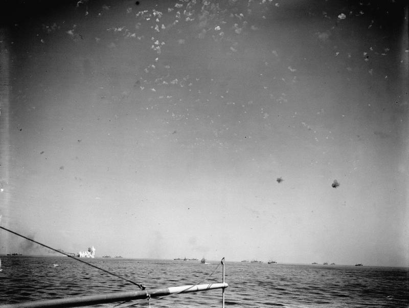 A photo from aboard HMS VICTORIOUS shows a stick of bombs falling near a merchant ship, left, as the sky is filled with flak bursts.