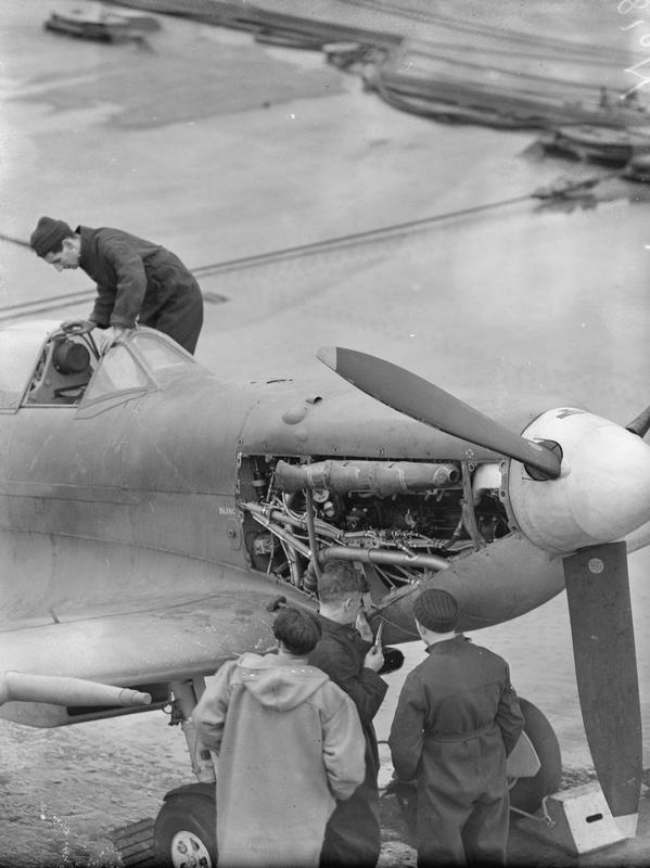 Fleet Air Arm mechanics carrying out adjustments to the engines of a Seafire aboard HMS VICTORIOUS in September, 1942.