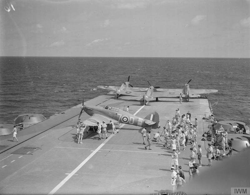 Deck crew position a non-folding Sea Hurricane on HMS INDOMITABLE's large forward lift. They had to be skewed sideways onto roller-rails to arrange them within the hangar.