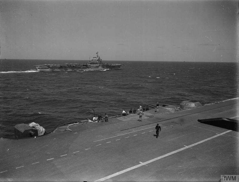 While the original caption states this is HMS VICTORIOUS as seen from the island of INDOMITABLE during Operation PEDESTAL, the identities are likely the other way around. (Only VICTORIOUS had the raised deck faring behind the 4.5in turrets, seen here with crew standing on it)