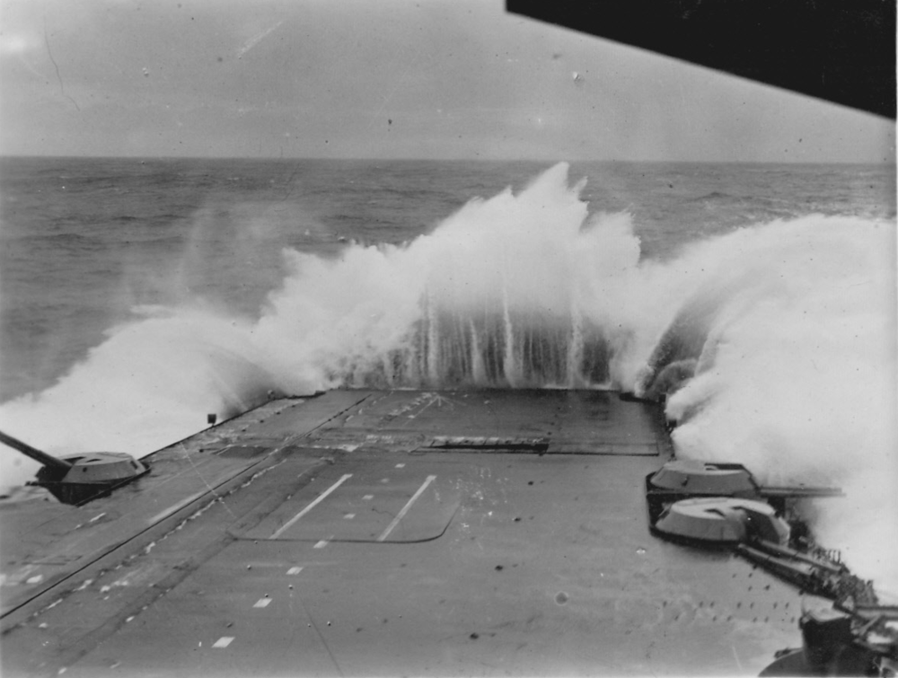 HMS VICTORIOUS encounters heavy weather, with waves breaking over her hurricane bow.