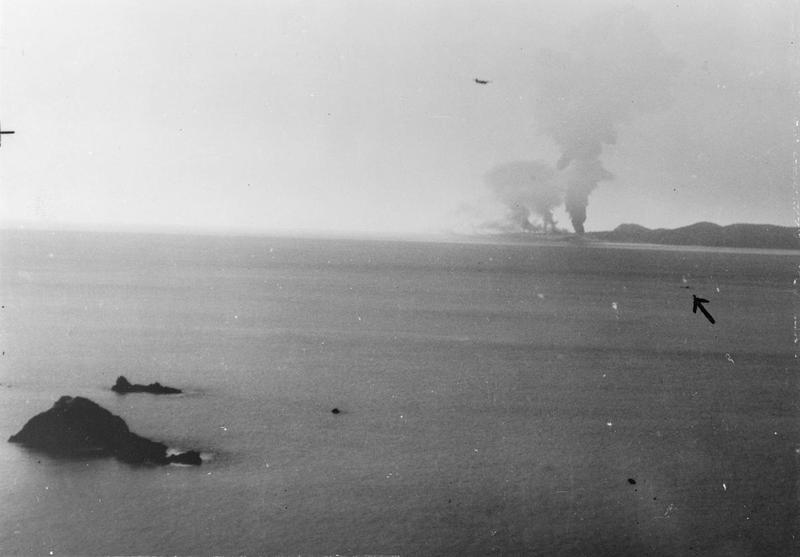 Sabang burns in the background as HMS Tactician, indicated by the arrow right, moves up - under fire - to pull a downed US Hellcat pilot out of the water.