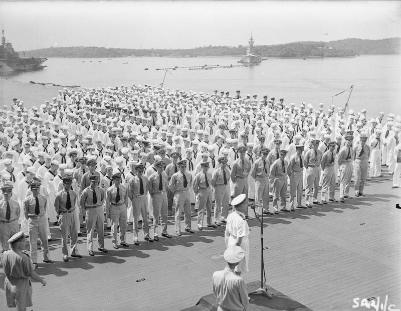 Admiral Somerville, RN, speaks to USS SARATOGA's crew in Trincomalee harbor. In the background are HMS ILLUSTRIOUS and RENOWN.