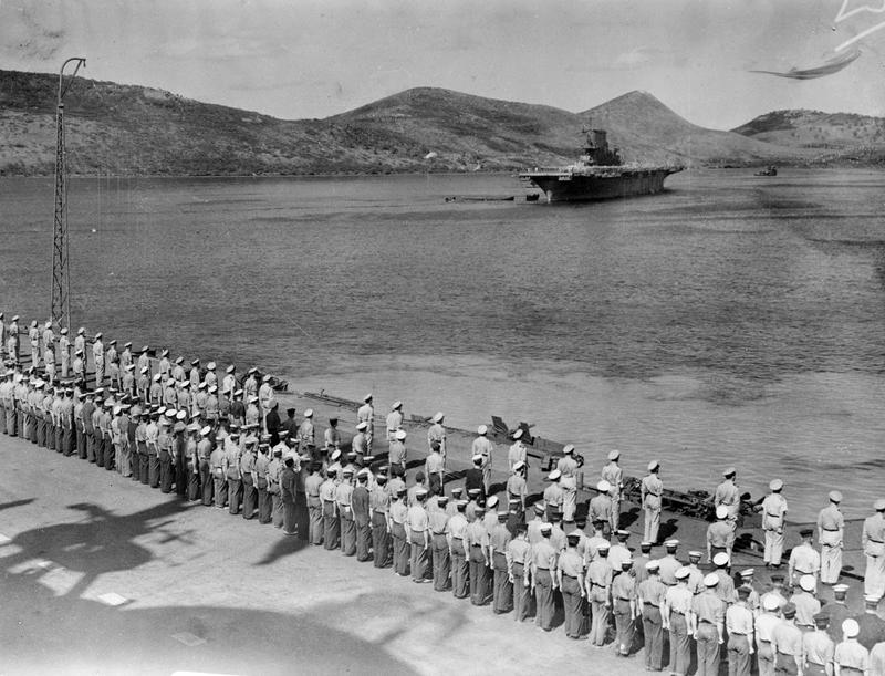 HMS Victorious's crew man the deck as the ship leaves Noumea for the last time.