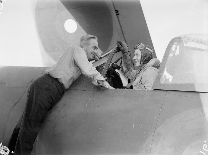 Mr Thomas Stanton, a civilian engineer who joined ILLUSTRIOUS in December 1943, as Technical Advisory Representative for Chance-Vought Corsairs, chatting to pilot Sub Lieut (A) A W Sutton, of Saskatoon, Canada, after his return from the attack on Surabaya.
