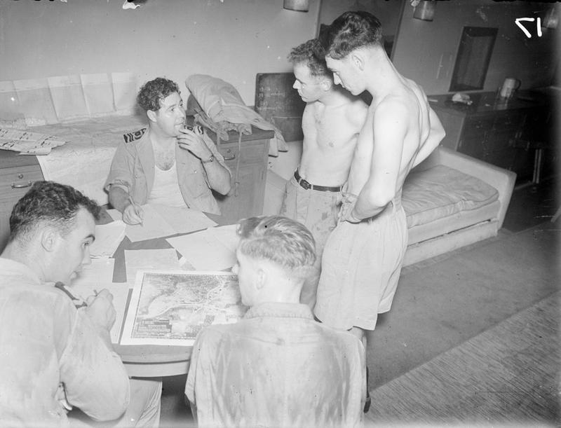 FAA Corsair pilots 'debrief' in HMS ILLUSTRIOUS's wardroom after returning from the raid on Surabaya