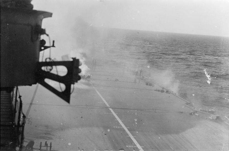 This picture is the first in a sequence of two which shows the flight deck of ILLUSTRIOUS after she was hit on the armoured flight deck and in the aft liftwell. It has been incorrectly dated in the IWM archive. The white smoke emerging from the centreline is from the 19in hole created by the 2200lbs hit, while the grey smoke from the right of the image is likely from the burning bow. The toppled lift is in the background, jutting upwards against the smoke.