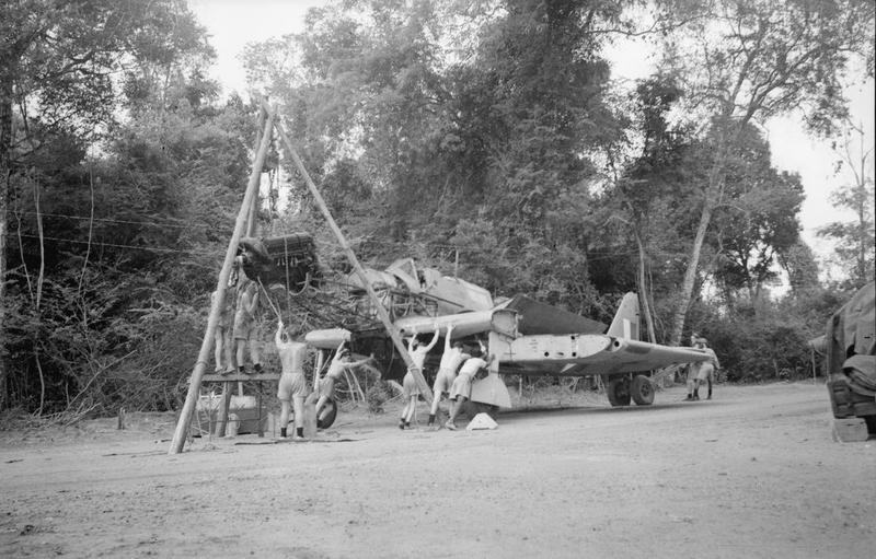 Fleet Air Arm maintenance ratings removing the engine from a Fairey Fulmar naval aircraft with the aid of a block and tackle against the background of jungle at China Bay.