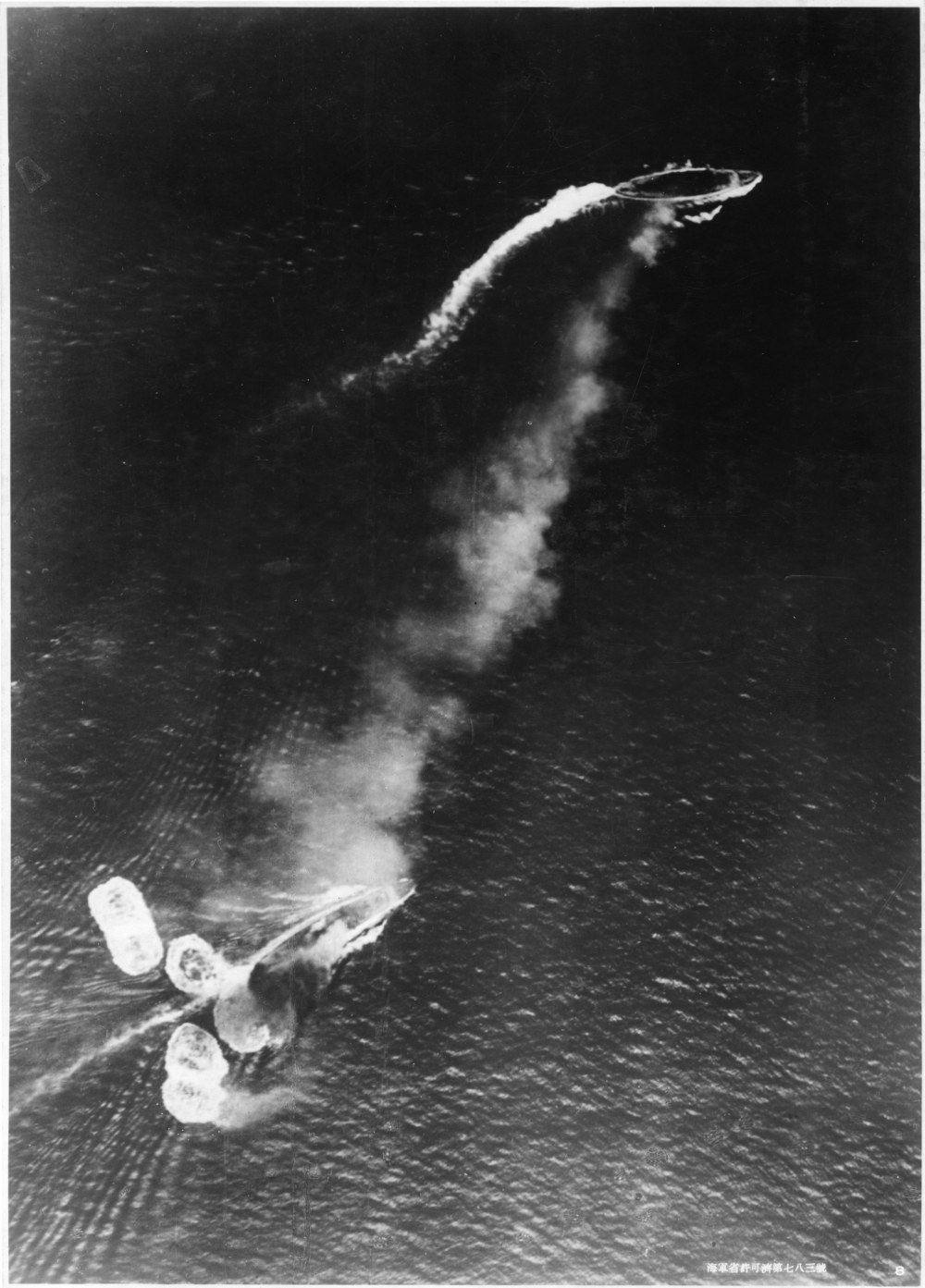 Photograph taken from a Japanese aircraft during the initial high-level bombing attack. Repulse, near the bottom of the view, has just been hit by one bomb and near-missed by several more. Prince of Wales is near the top of the image, generating a considerable amount of smoke. Japanese writing in the lower right states that the photograph was reproduced by authorization of the Navy Ministry.