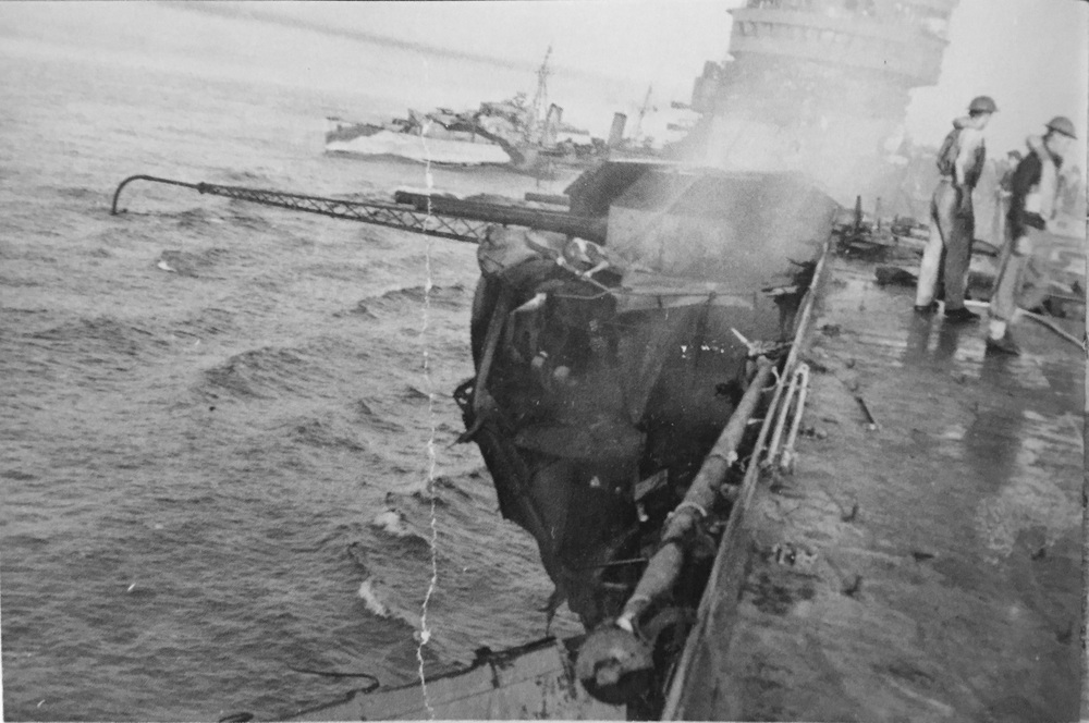 HMS INDOMITABLE's disemboweled A1 turret, shortly after damage control parties doused the flames. HMS CHARYBDIS is crossing the carrier's stern. Picture: FAA Museum