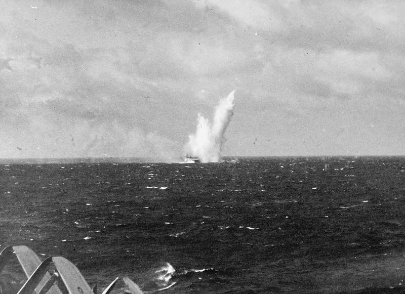 A kamikaze explodes in the ater alongside HMS Victorious, as seen from HMS Illustrious.