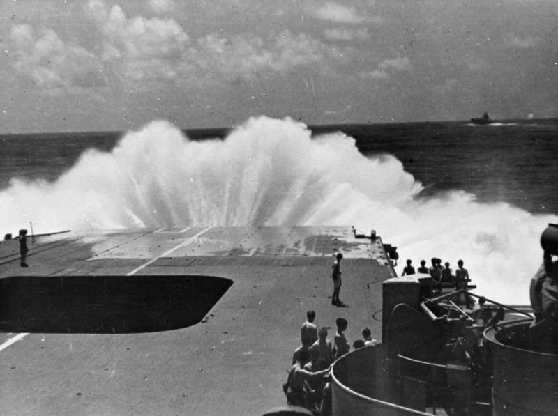 A British Pacific Fleet aircraft carrier gets her nose well down to a heavy sea.