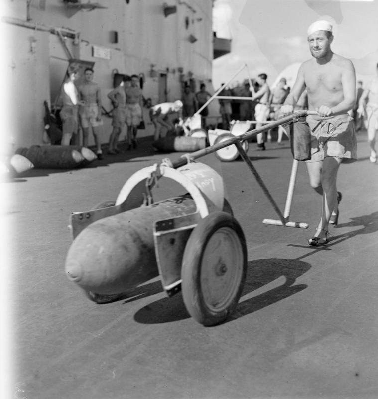 Steward K Mallinder, of Sheffield, wheeling a 500 pounder during bombing up in preparation for the strike on Belawan Deli.