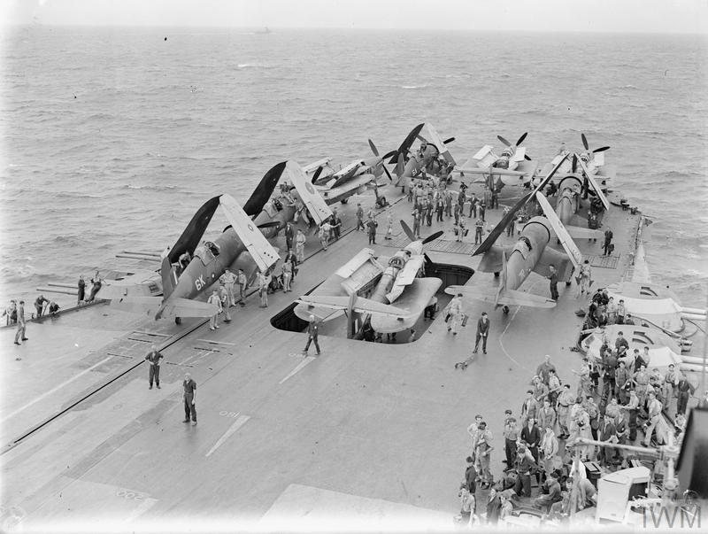 Barracudas and Corsairs on the forward end of the flight deck of the ILLUSTRIOUS being stowed after the raid. A Fairey Barracuda is on the lift going down the hangar.
