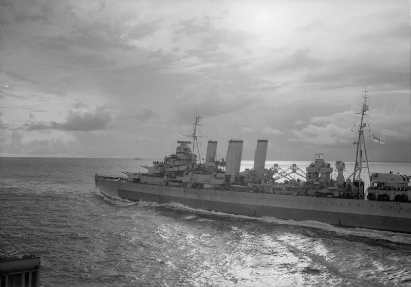 The cruiser HMS CUMBERLAND off Car Nicobar island at sunset.