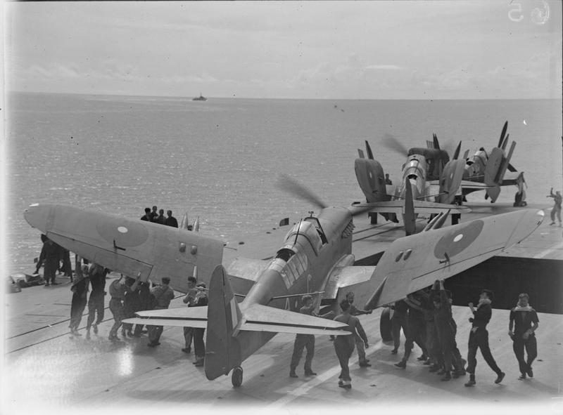 Men folding the wings of a Fairey Firefly of 1770 Squadron, Fleet Air Arm on board HMS INDEFATIGABLE on the aircraft's return from the carrier-borne air strike on the Japanese oil refinery at Pangkalan Brandan, Sumatra. Weather conditions were excellent and the whole weight of bombs and missiles from the Grumman Avengers and Fairey Fireflies fell within the target area. The powerhouse and other important plants, together with oil tanks and buildings, received direct hits.