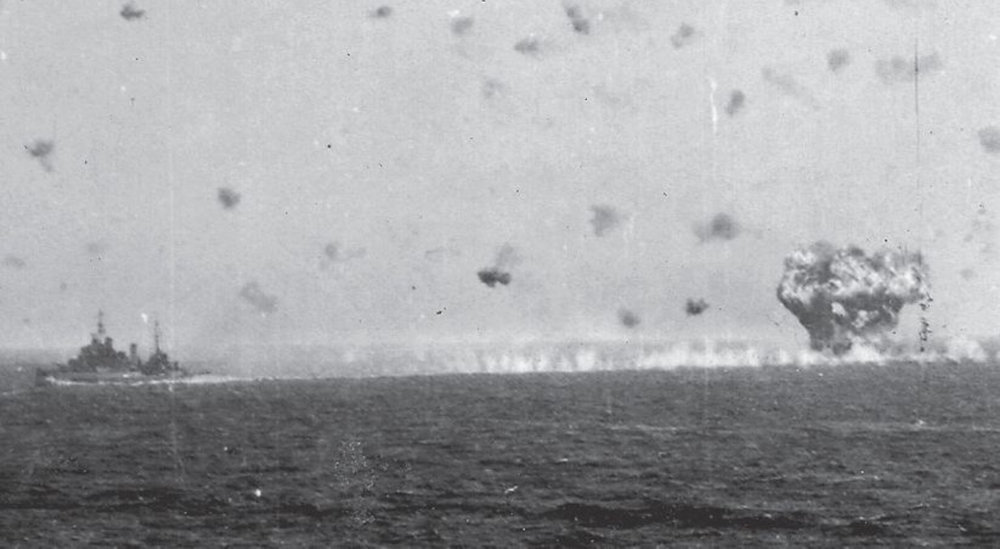 HMS FORMIDABLE vanishes behind an eruption of fire and smoke after a kamikaze and its 500lb bomb struck the armoured flight deck amidships.