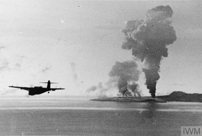 A Fairey Barracuda leaves huge fires, showing the success of the attack, as it returns from the raid.