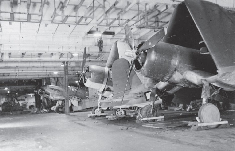 Inside UNICORN's hangar. Here she has three Corsair's tightly stowed, with two Firefly fighter-bombers in various states of assembly in the background.