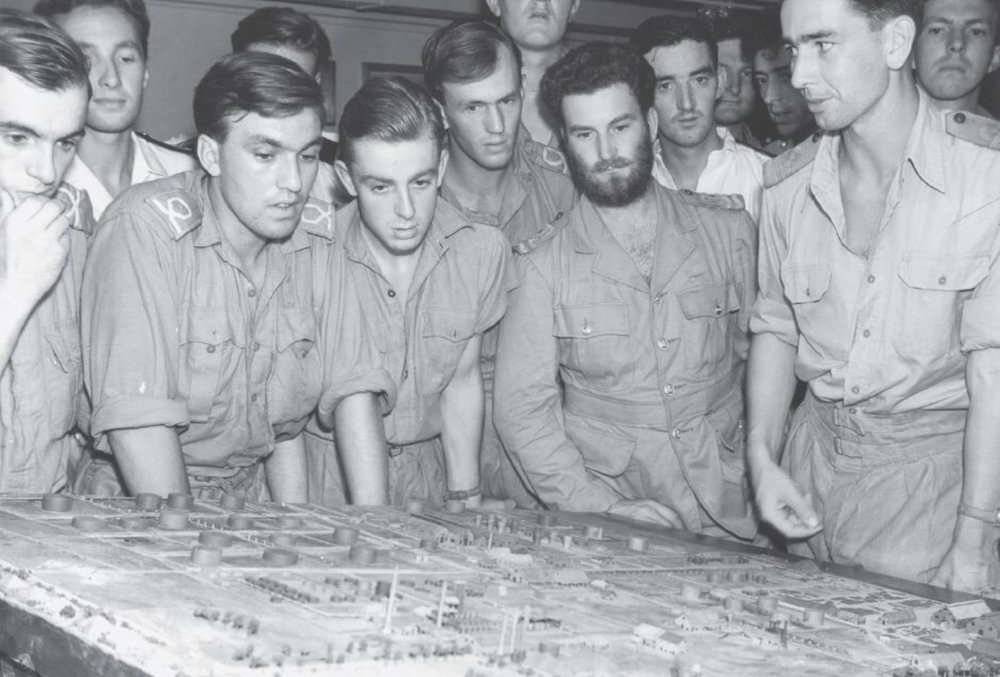 Lieutenant Commander Mainprice, right, briefs the pilots and aircrew of 854 Avenger squadron over a detailed model of the Pladjoe oil refinery aboard HMS Illustrious shortly before Operation Meridian I.