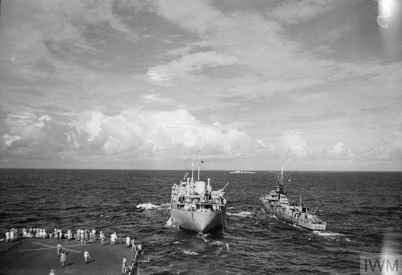 A fleet auxiliary, HMS EMPIRE SAVAGE, refuelling a destroyer (HMS WAKEFUL) alongside while HMS ILLUSTRIOUS refuels using the line-astern method. In the distance is the cruiser HMS ARGONAUT.