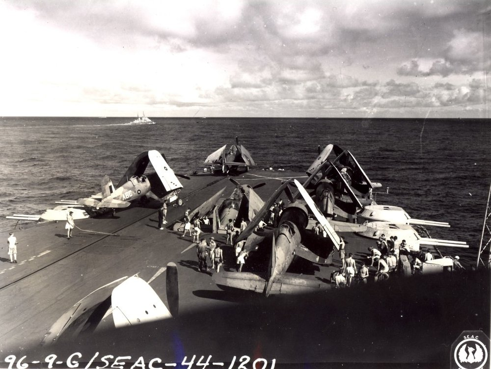 Corsairs and an Avenger wait their turn being struck below as another Avenger is lowered on the forward lift.