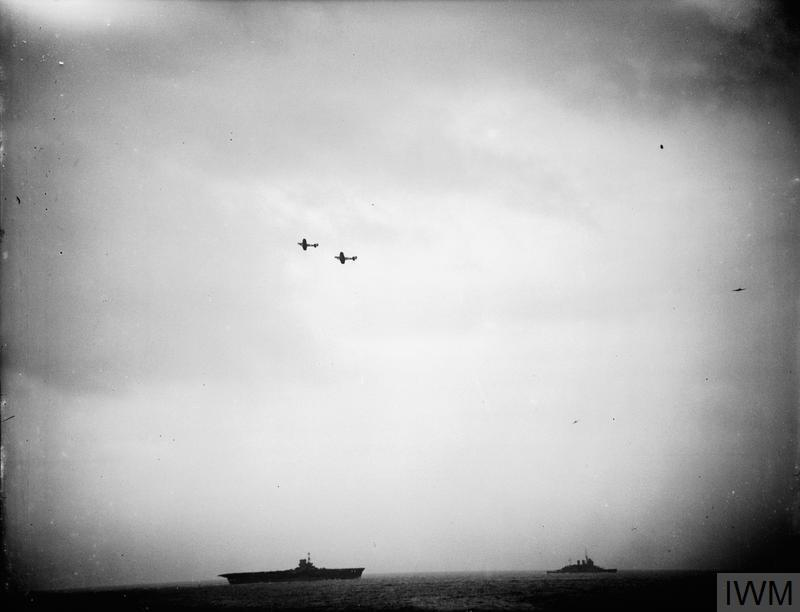Fairey Fulmar fighters patrolling above HMS ARK ROYAL and HMS RENOWN during an attack on a British convoy in the Sicilian Channel, 1941.