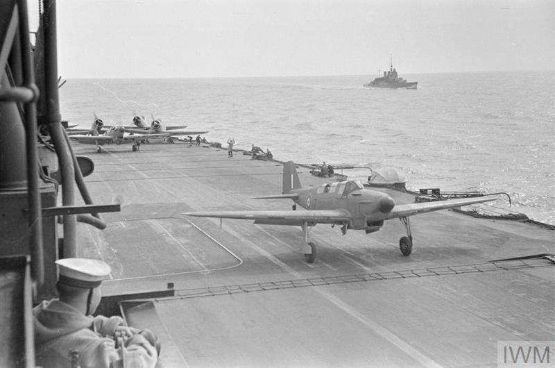 Fulmars and Skuas flying off with HMS ARK ROYAL early in 1941. The battlecruiser (rebuilt as a carrier escort) HMS RENOWN is in the background.