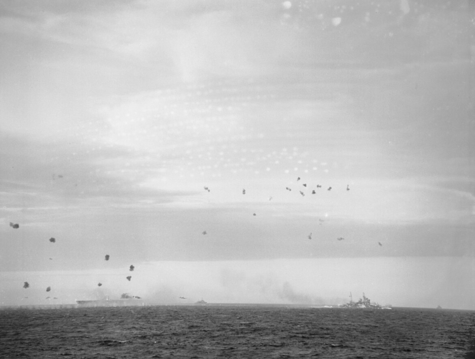 ARK ROYAL's outline is barely discernable against the spray and smoke, left, as a battleship - probably QUEEN ELIZABETH and a Town-class cruiser help defend her with an umbrella-barrage.