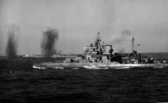 Bombs fall between HMS VALIANT and an escorting cruiser and destroyer.