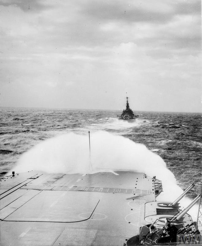 HMS IMPLACABLE in heavy weather astern of HMS VANGUARD in 1946