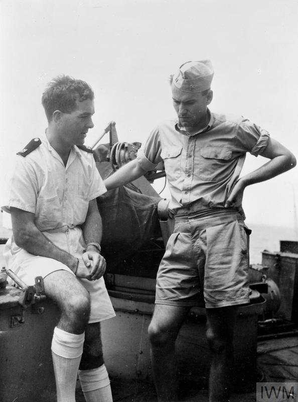 The Ship's Chaplain, Rev J Trainer, talking with the ship's US Navy Liaison Officer Lieut W E Rayne, on the fo`c'sle of the FORMIDABLE, August 1945.