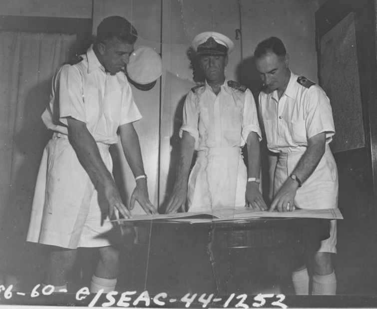 Shot made on HMS INDOMITABLE by Lt Bennett: Left to right: Capt I.A.S. Eccles, Admiral Vian, and J.P. Wright, Commander, Admirals Chief of Staff, looking at chart in captain's cabin. SEAC Photo Unit (US).