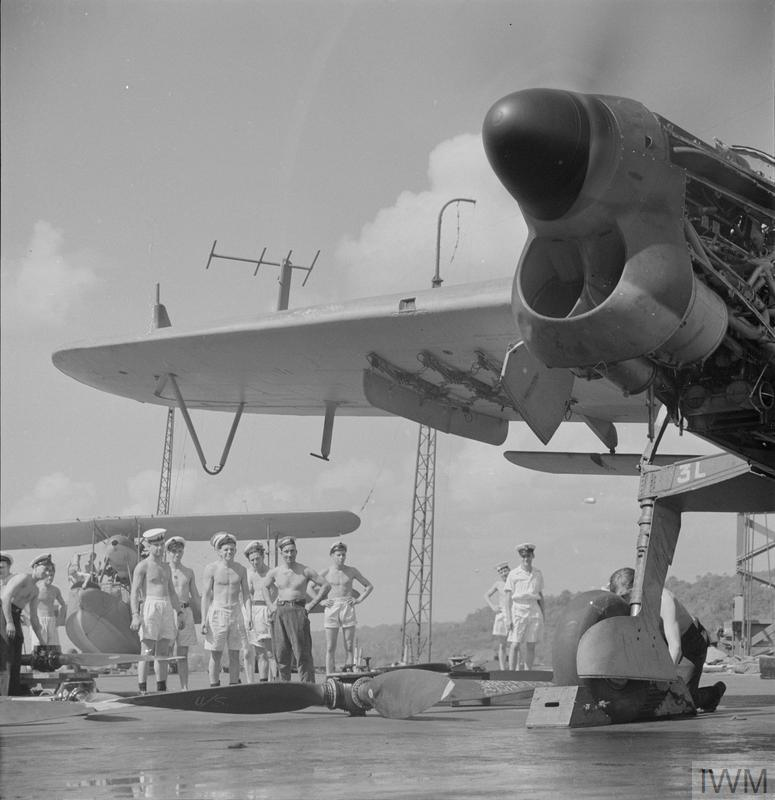 HMS UNICORN, Trincomalee , February 1944: A new air screw has been fitted to a Barracuda and an engine test is made while repair crew stand by. Note the surface-search radar on the Barracuda's wing. A Walrus is on the deck in the background.