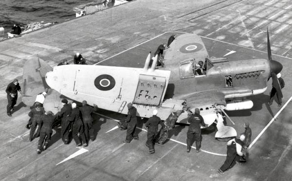 A Firefly FR1 has its wings folded aboard an escort carrier. The box-like container under the cannons is a RATO mechanism.