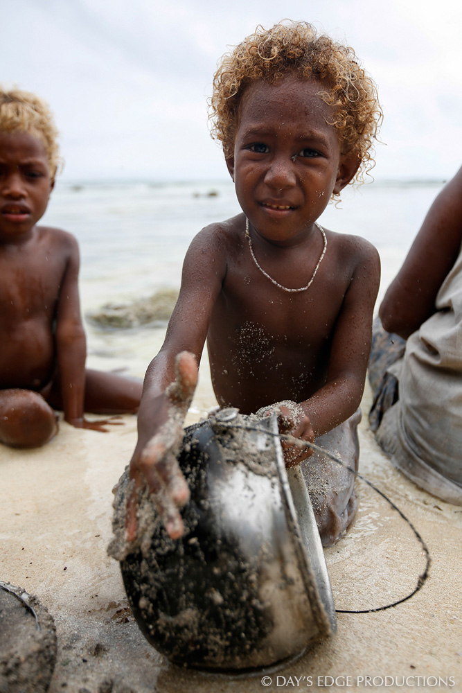 A village boy scrubs a pot with beach sand on Santa Catalina Island, Solomon Islands. Recent research shows that the blonde hair of many Solomon Islanders is dictated by a different gene than is blonde hair in Europeans.