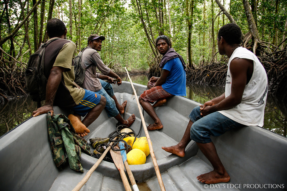 Dr. Albert Uy's research assistants guide a small boat through a mangrove channel on Makira Island, Solomon Islands.