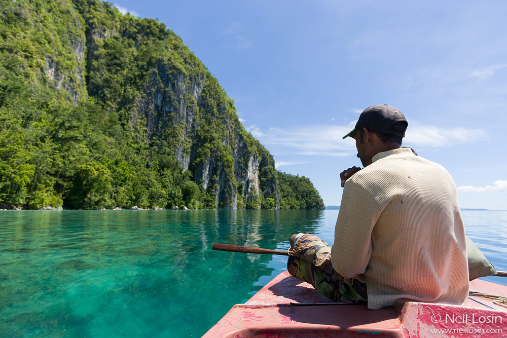 A local guide pilots a small boat along limestone cliffs on the island of Seram, Indonesia.