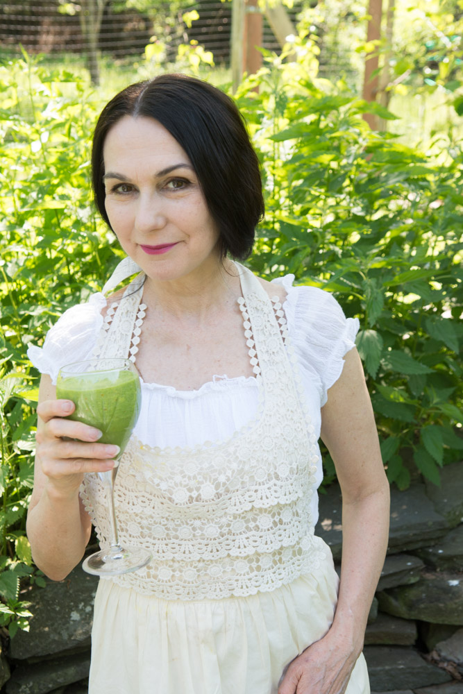 Sharon with a  Love Smoothie  and a backdrop of wild nettles at the Wild Woodstock Forest Sanctuary #3. Photo by Derek Pashupa Goodwin.