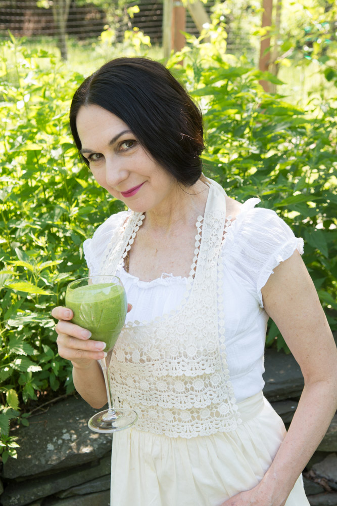 Sharon with a  Love Smoothie  and a backdrop of wild nettles at the Wild Woodstock Forest Sanctuary #4. Photo by Derek Pashupa Goodwin.